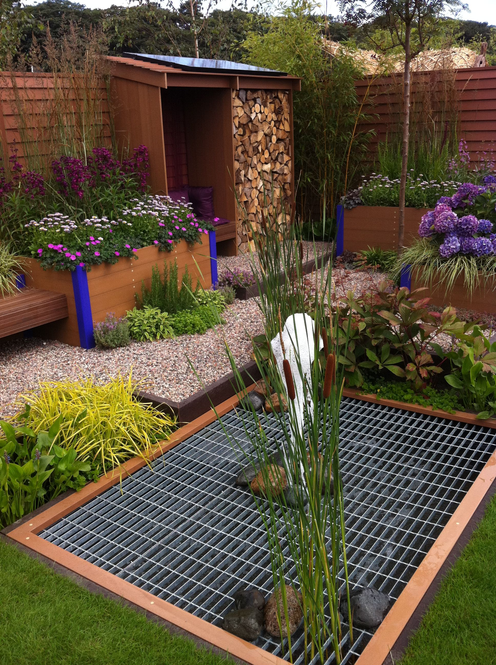 Lovely low maintenance garden idea. Really love the log store ...
