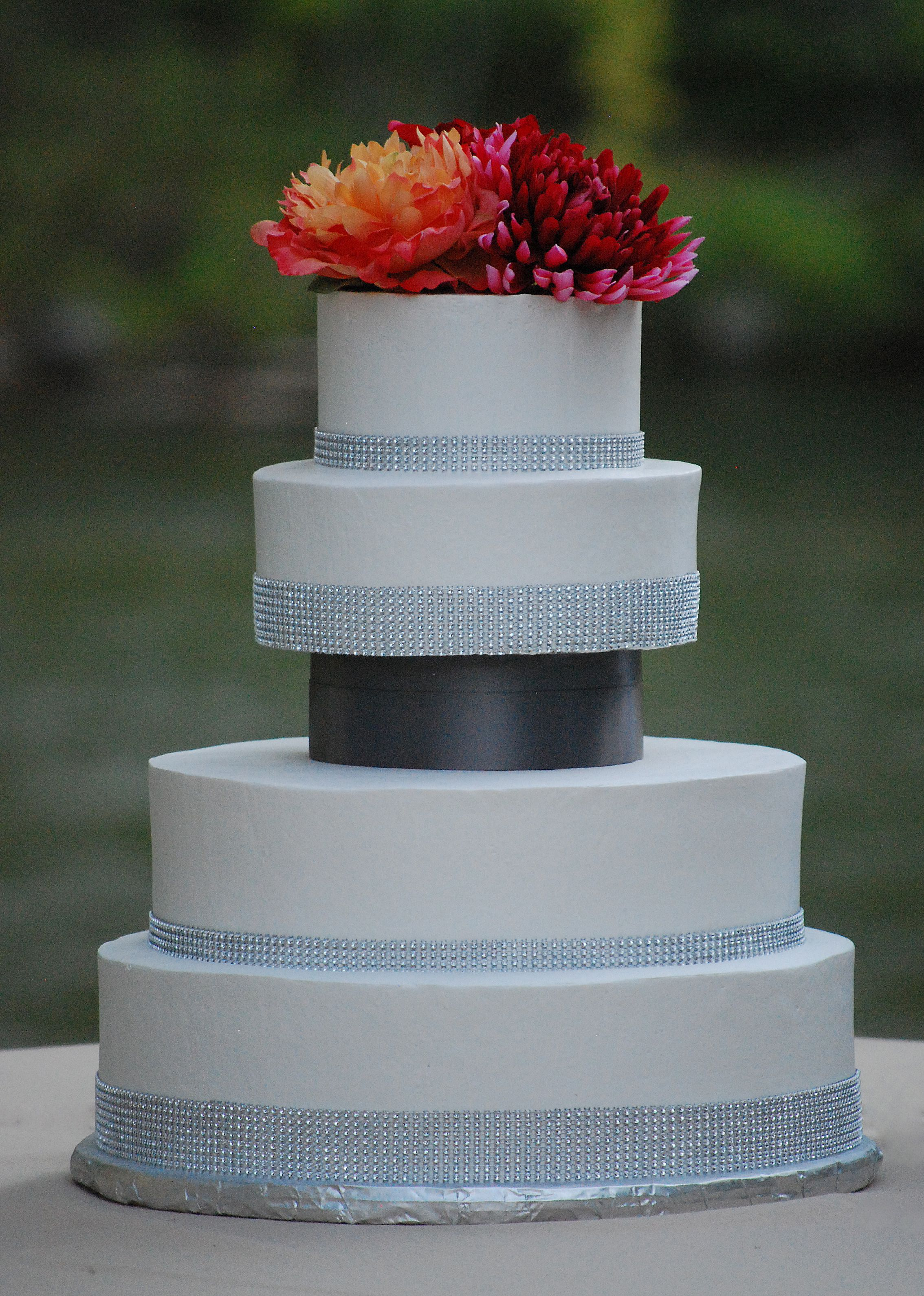Round Wedding Cake With Silver Bling Borders Bold Orange And Pink Flowers