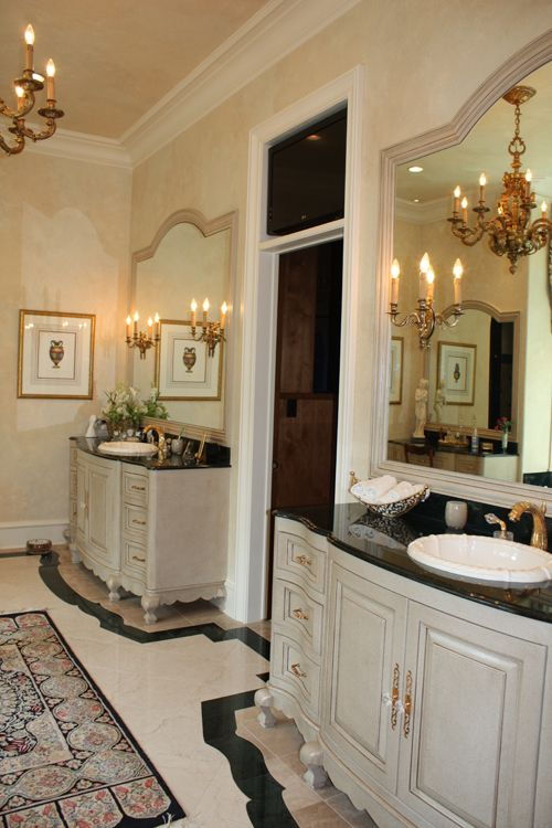 Beautiful vanities. Love the sconces on the mirrors, the way the floor detail outlines the shape of the vanities.