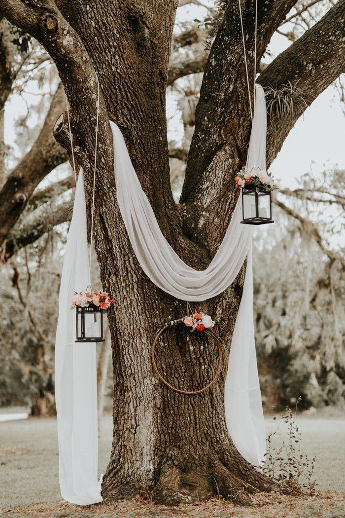 Gedrapeerd wit linnen, hangende lantaarns en bloemenkransen creëren …