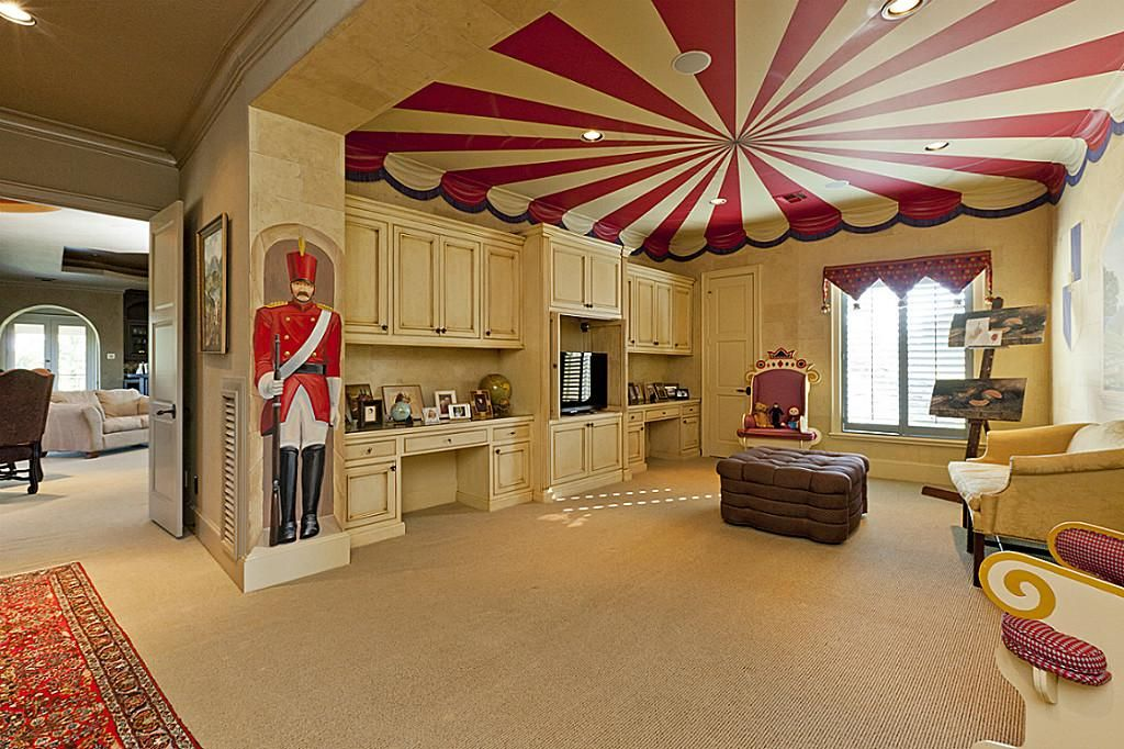 Whimsically painted kids' game room / play room with built-ins, two desks, and huge closet.