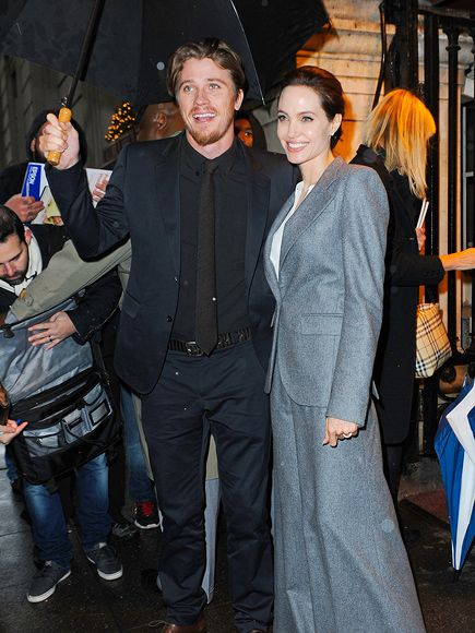 TAKE COVER   Such a gentleman! Actor Garrett Hedlund shields Angelina Jolie from the New York City rain on Tuesday at a screening of Unbroken.