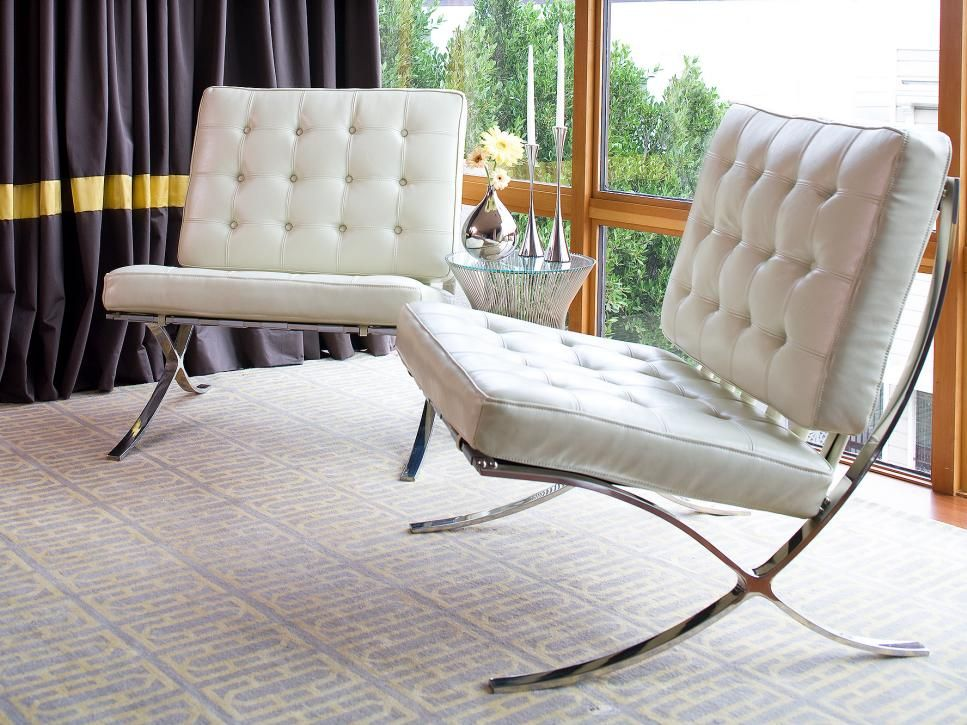 A pair of tufted white leather chairs create a chic, mid ...