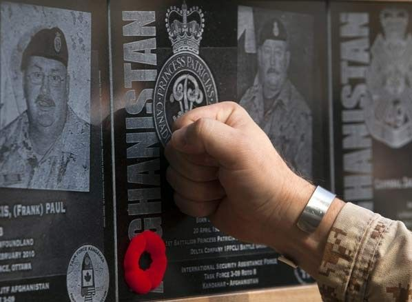 A soldier touches the plaque of a fallen comrade at the war memorial after the last Remembrance Day ceremony at Kandahar Air Field. (Ryan Remiorz/The Canadian Press)