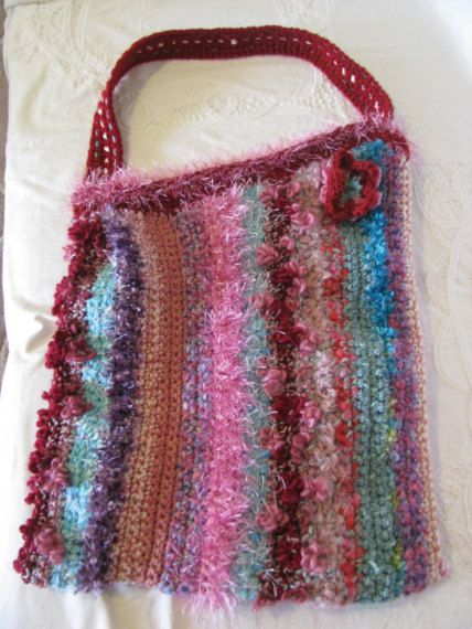 $55.00 Crochet lined tote with pocket sewn into the lining. Crochet novelty yarns in colours of Aqua, maroon, pink, purple, cream, cherry, blue.. $55.00, via Etsy.