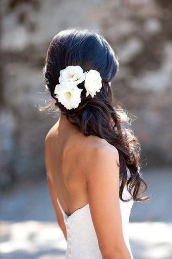 Recogido en parte de atrás de la cabeza con flores y melena con caída en cascada de ondas muy abiertas