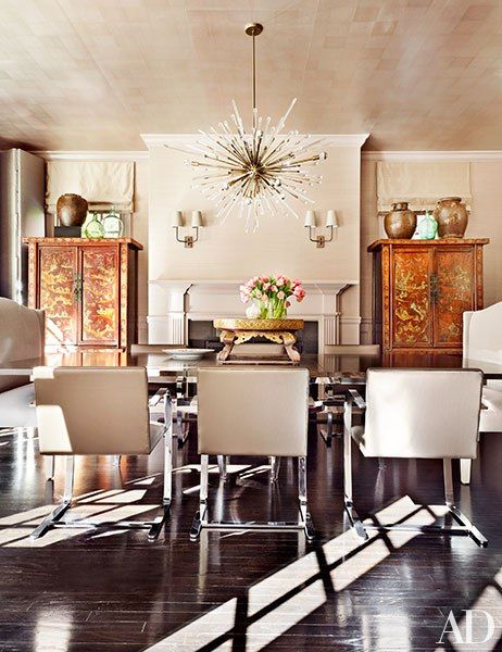 Allyson and Jonathan Simon enlisted designer Vicente Wolf to bring a contemporary feel to their traditional house in New York's Westchester County. In the dining room, a Venfield chandelier hangs above a suite of Ludwig Mies van der Rohe chairs by Knoll from Design Within Reach; the ceiling is clad in a gilded tea paper from Stark.