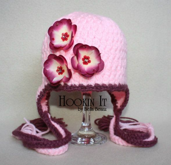 Pink crocheted photography prop hat with flowers and braided tassels