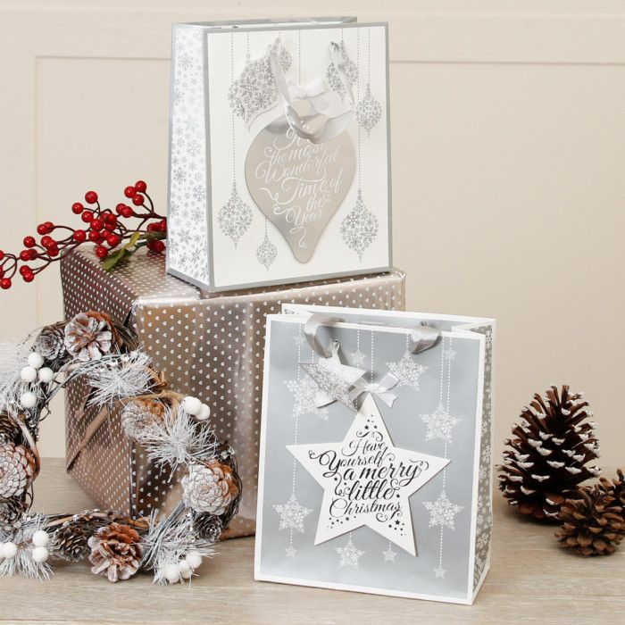 this set of 2 gift bags features a festive christmas message on a stylish design with ribbon handles and a matching gift tag