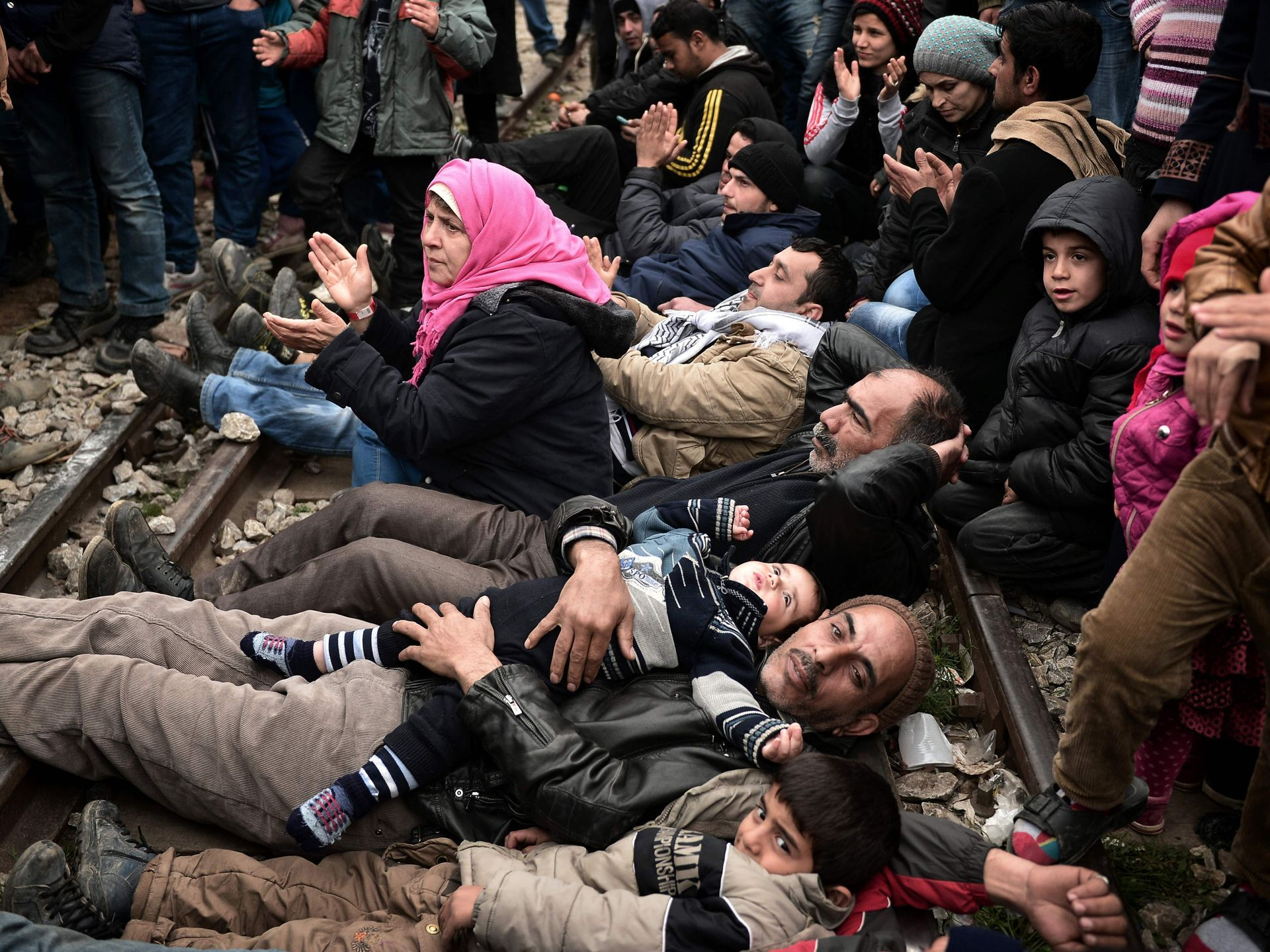 """Syrian and Iraqi refugees trapped at the Greek-Macedonian border lie on railroad tracks during a protest demanding the opening of the Idomeni crossing. Greece warned the number of refugees and migrants on its soil could more than triple next month, reaching as many as 70,000, as a Balkan cap on border crossings left thousands """"trapped"""" in the country.   Louisa Gouliamaki, AFP/Getty Images"""