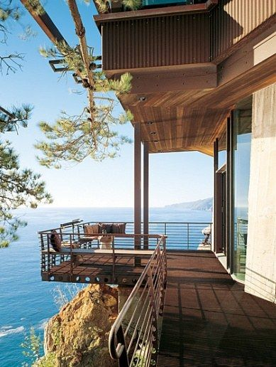 Characterized by its dramatic cliffside setting and rebuilt by architect Mickey Muennig, a couple's house in Big Sur, California, serves as a calming retreat. Above: A view to the north across the western elevation of the residence, which is crafted of concrete, steel, glass and wood. The couple spend much of their time in Big Sur on the deck, watching and listening for wild creatures in the refuge below. (October 2004)