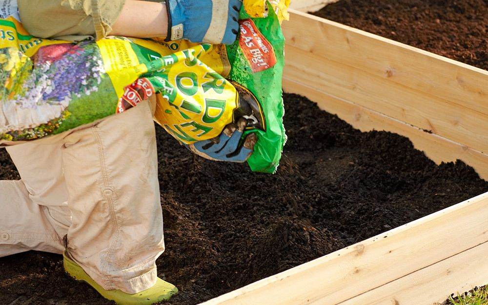 Garden soil being poured into a raised garden bed