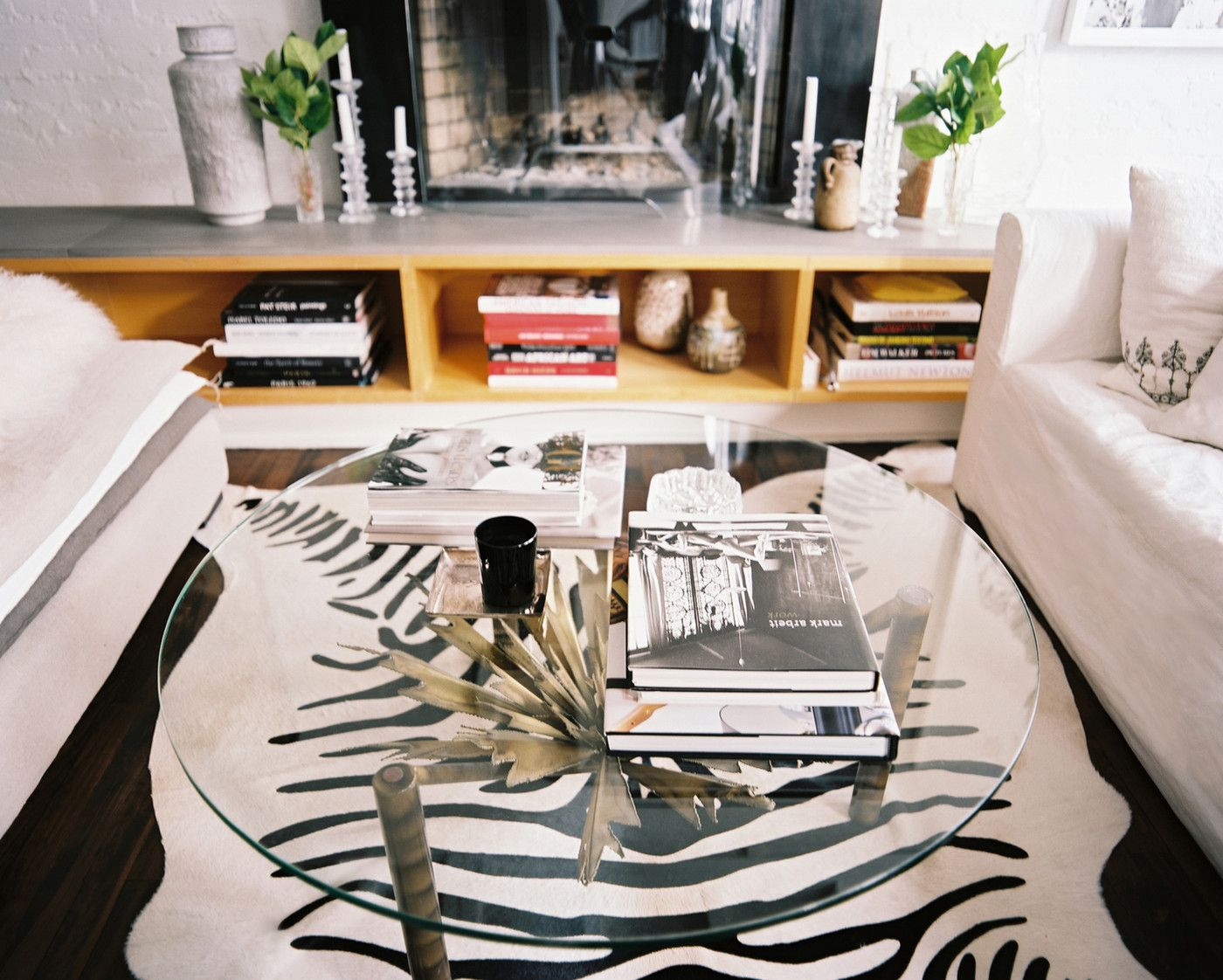 Modern Urban  Coffee Table: A glass coffee table atop a zebra-print rug in a neutral living space.