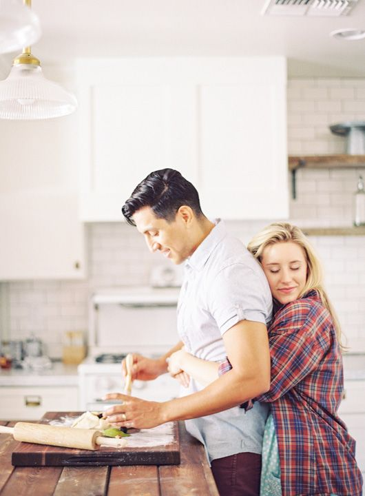 She hugs him from behind as he cooks. Intimate kitchen engagement shoot. - Melissa Jill Photography