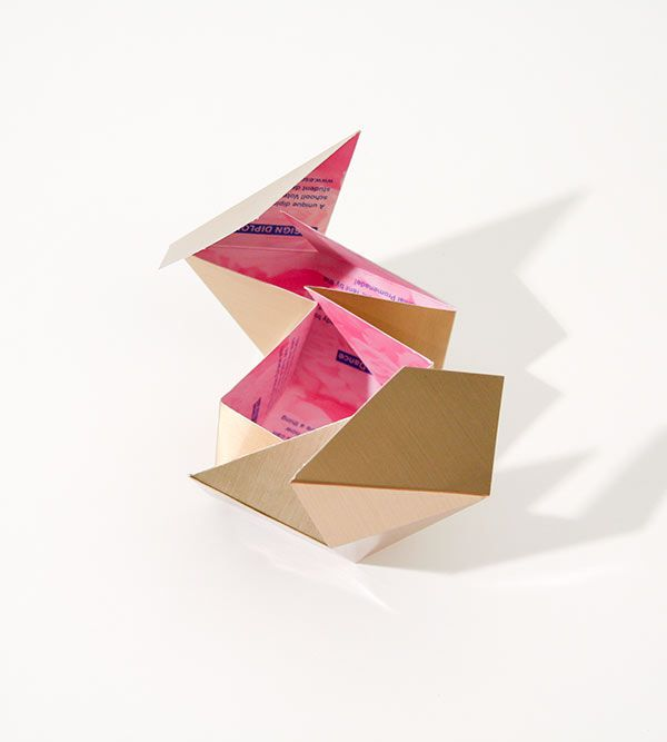 A Promotional Flyer That Folds Into A Cube Held By A Rubber Band