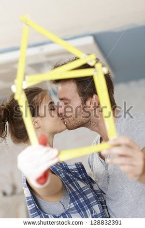 Kissing couple forming little house of ruler, renewing home.