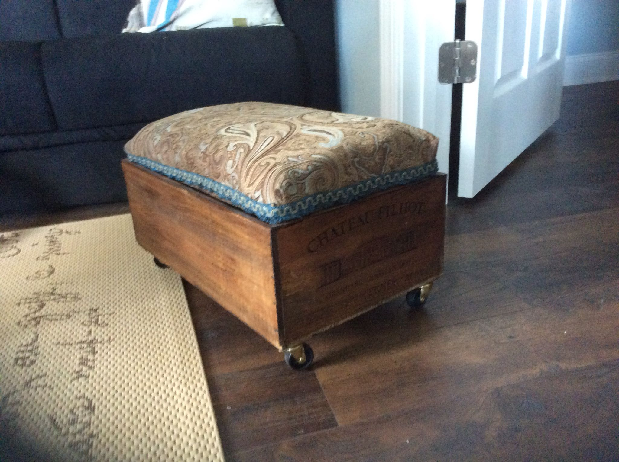 Wine crate that I added castors and an upholstered top to. Top can be removed for storage.