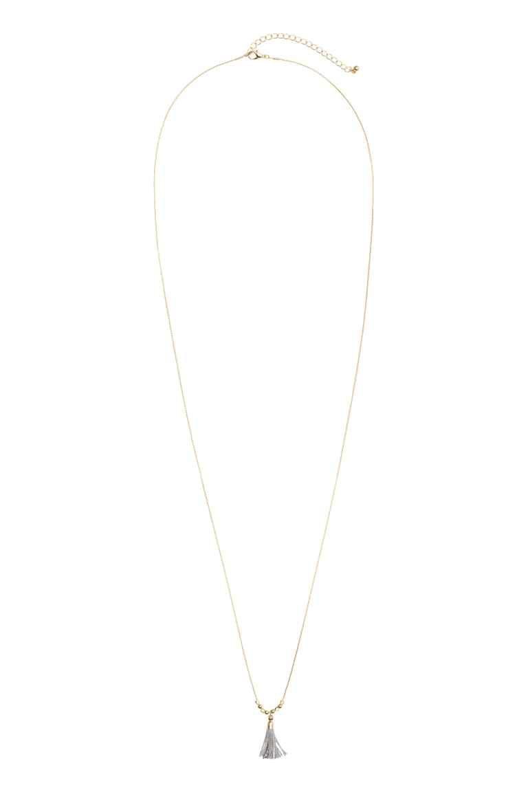Lange Halskette: Feine Halskette aus goldfarbenem Metall. Die Kette hat einen Metallanhänger mit Quaste und auf beiden Seiten davon vier Plastikperlen. Verstellbare Länge, 97-105 cm.
