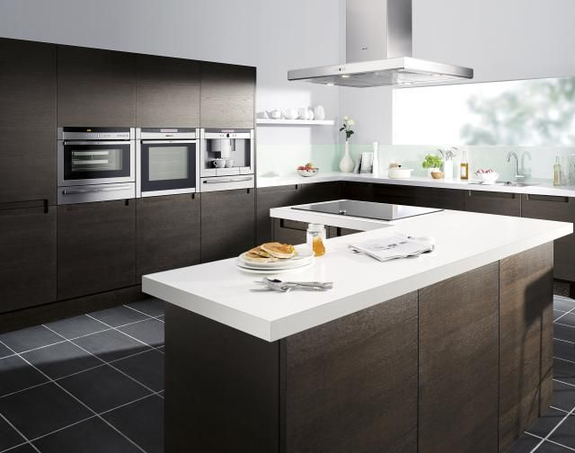 En una cocina amplia, atrévete con un mueble oscuro y una encimera ...