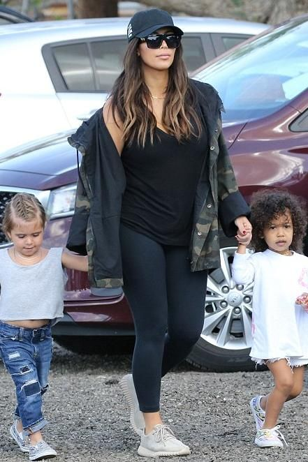 Kim Kardashian wearing T by Alexander Wang Classic Mini Pocket Tank, Celine Cl 41756s Zz Top Sunglasses, Lululemon Align Pants in Black, Anti Social Social Club Weird Cap in Black, Yeezy Camouflage Coat and Adidas Yeezy 350 Boost Sneakers in Moonrock