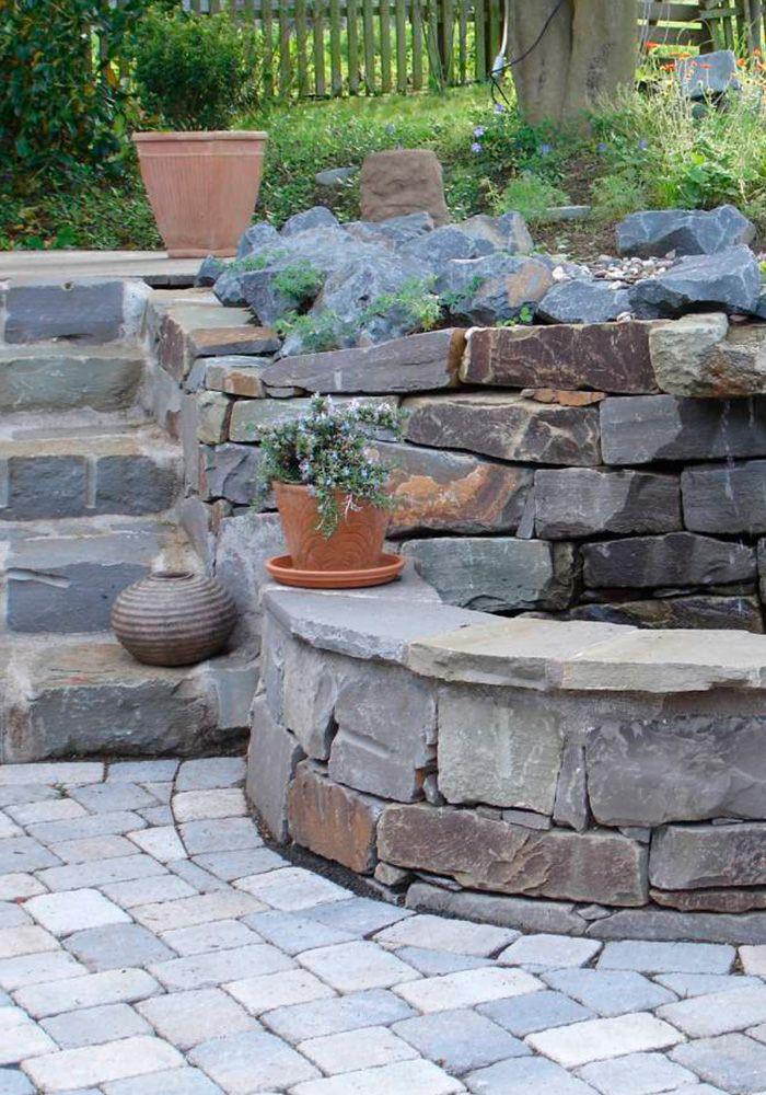Verwunschener Krautergarten Mit Brunnen Und Hochbeet Aus Naturstein Brunnen Garten Garten Steinmauer Garten