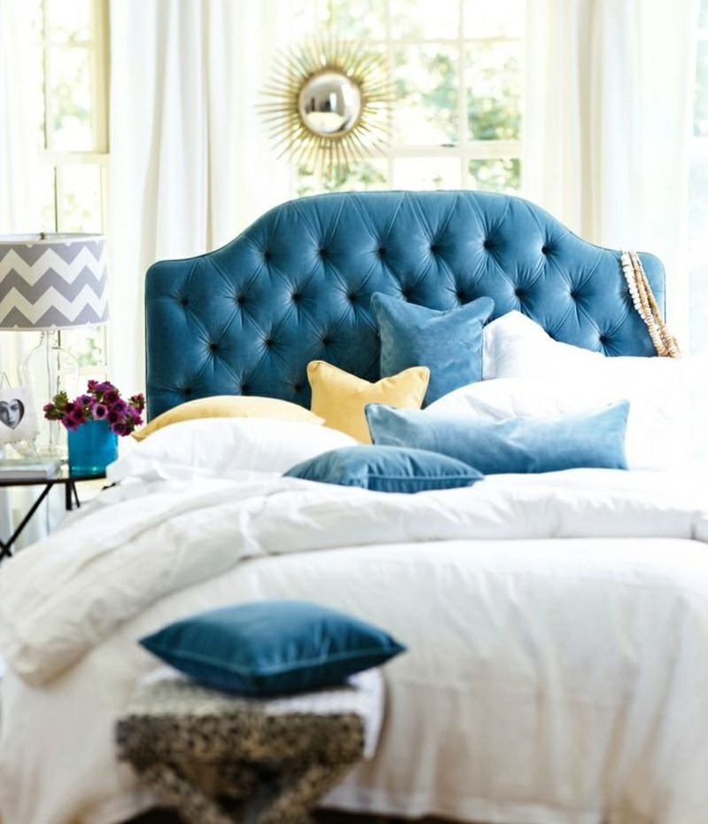 Blue velvet tufted headboard with yellow accents and white linens ...