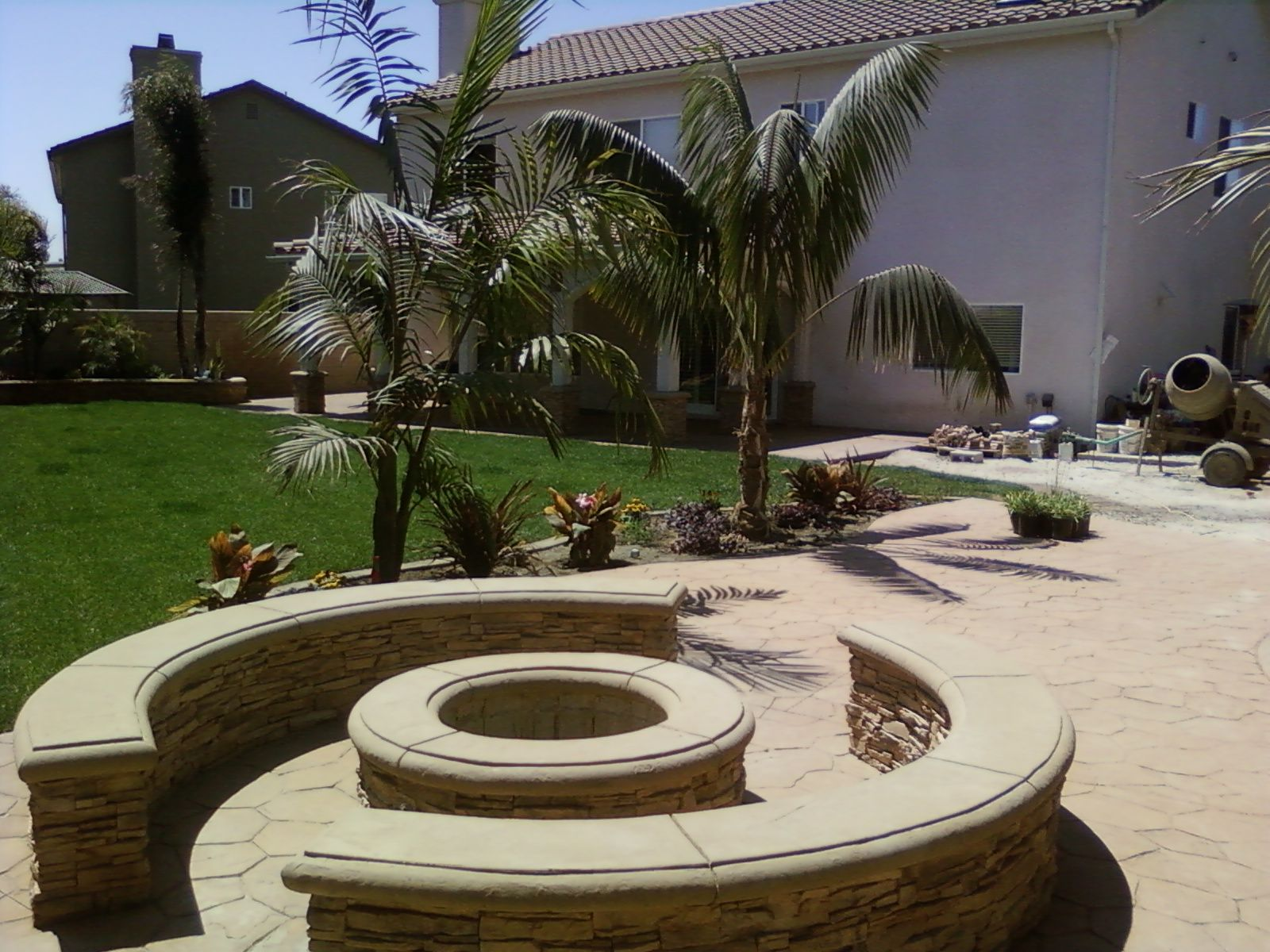 round fire pit with seat wall concrete cap and faux stone veneer