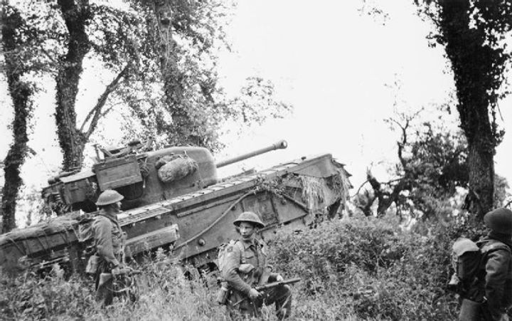 A Churchill tank of 7th Royal Tank Regiment 31st Tank Brigade supporting infantry of 8th Royal Scots during Operation Epsom 28 June 1944.