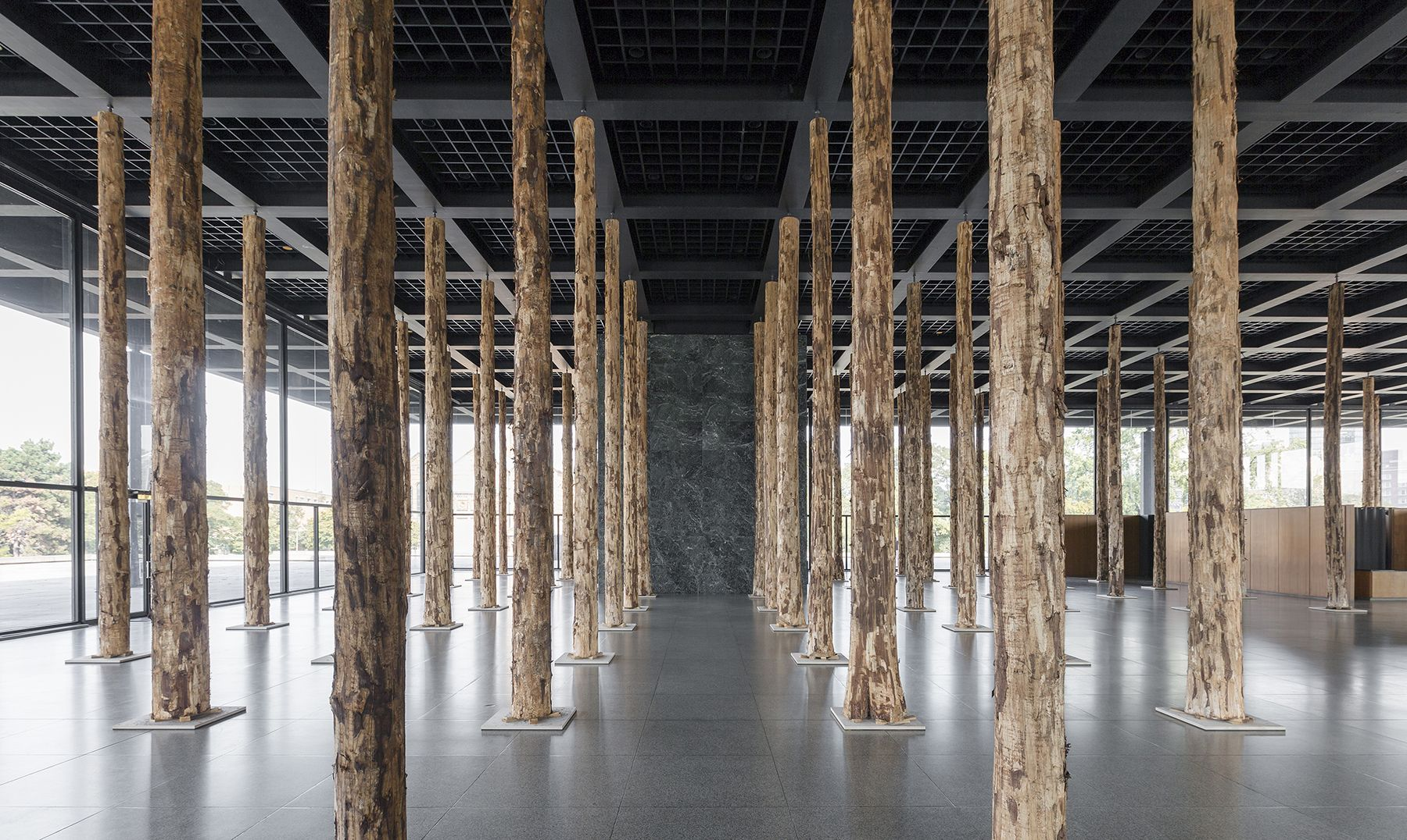 """Mies van der Rohe's Neue Nationalgalerie in Berlin gets a new """"structure"""" by David Chipperfield - Sticks and Stones, an Intervention using 144 imposing tree trunks, transforming the open glass hall of the museum into a densely filled hall of columns"""