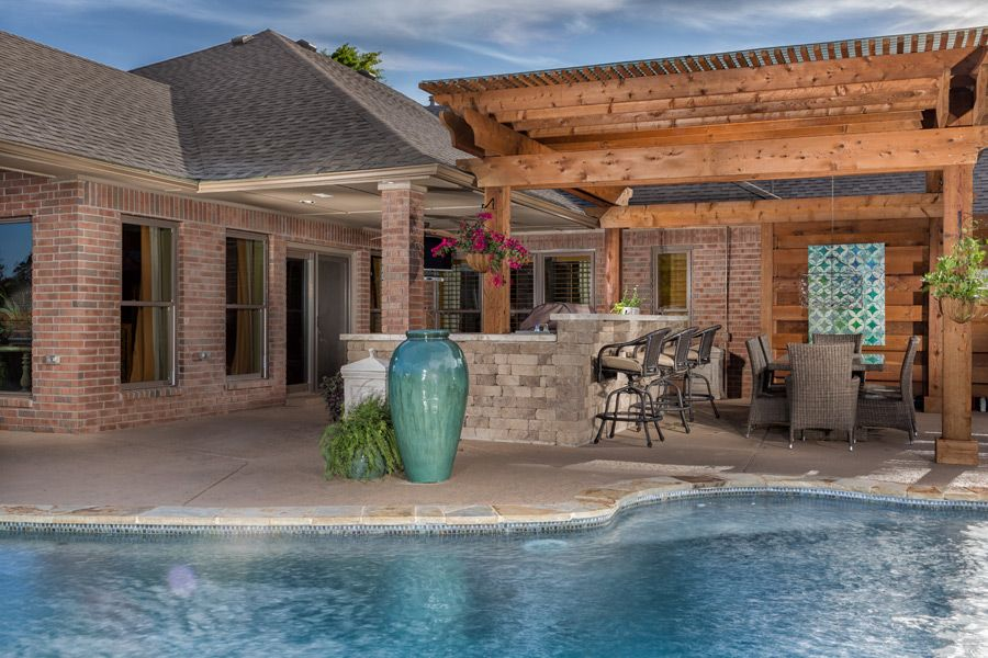 Tropical Outdoor Kitchen Under A Pergola Next To Pool Designed By Havenscapes Okc