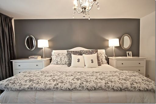 gray accent wall and white linens, white bedside tables, silver