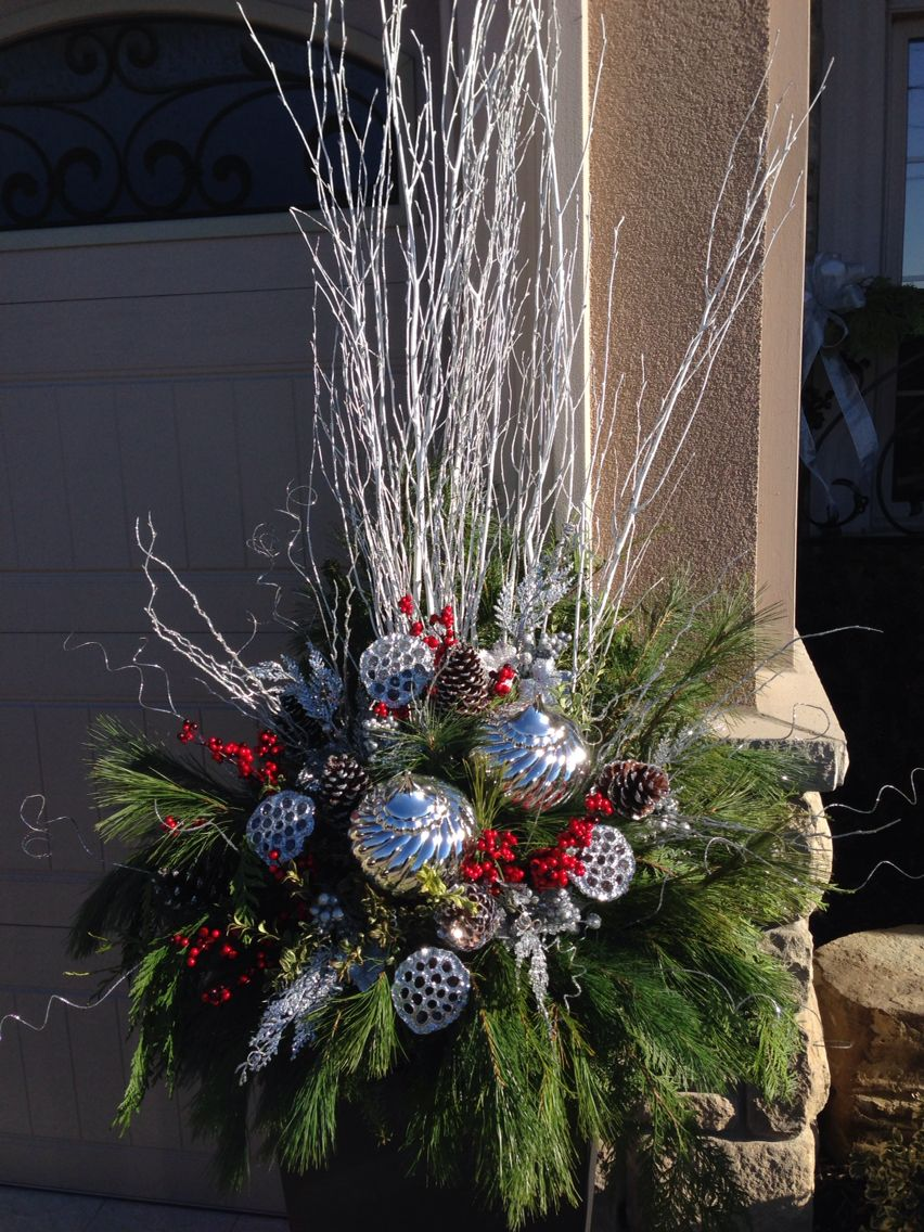 Silver galore - modern holiday silver ornaments accented with festive evergreens.