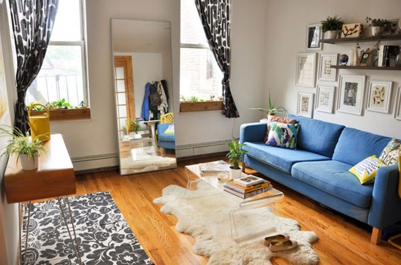 Window box indoors, blue couch, huge mirror and wood floors