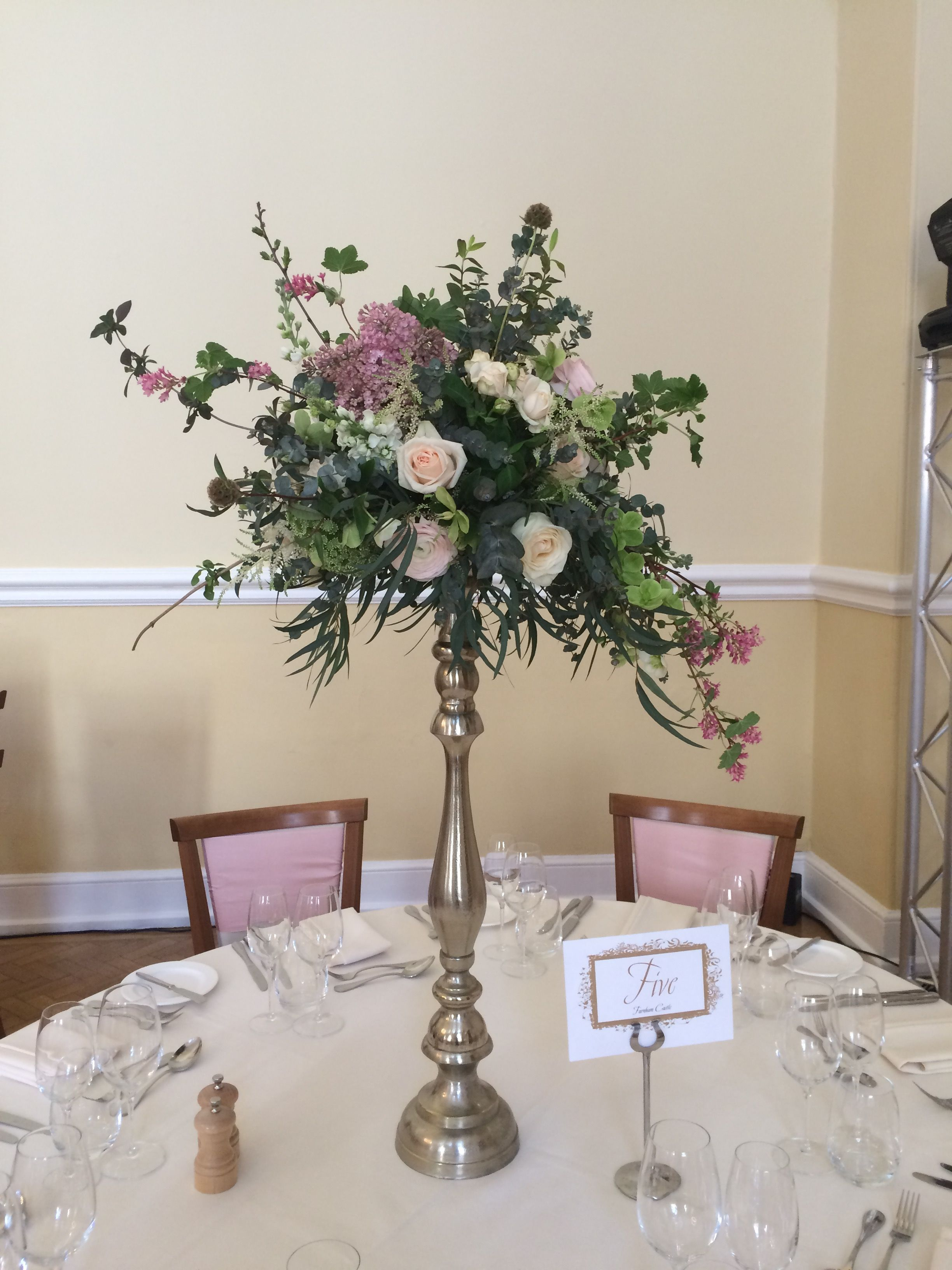 Tall floral design on a champagne gold stand, containing a mixture of seasonal foliage, scented Garden Roses Lilac, Scabious Pods, Stocks, Astilbe. Designed and created by www.hannahberryflowers.co.uk