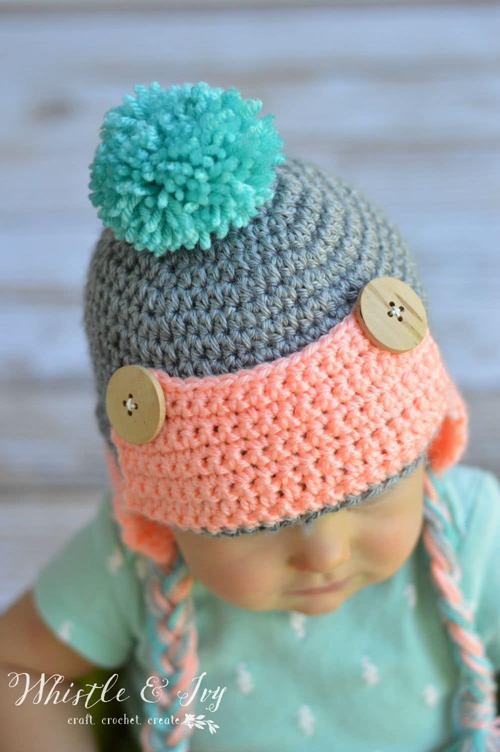 a7309bb3cfd Baby Button Trapper Hat - This cozy hat is a cute and fun baby accessory  for winter!  Free pattern by Whistle and Ivy