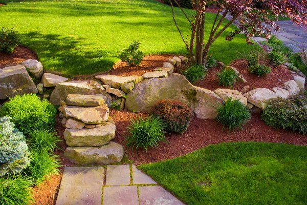 Landscaping On An Incline Doesn T Have To Be Difficult Irrigation And Ground Fortification Are Key Large Landscaping A Slope Sloped Garden Mulch Landscaping