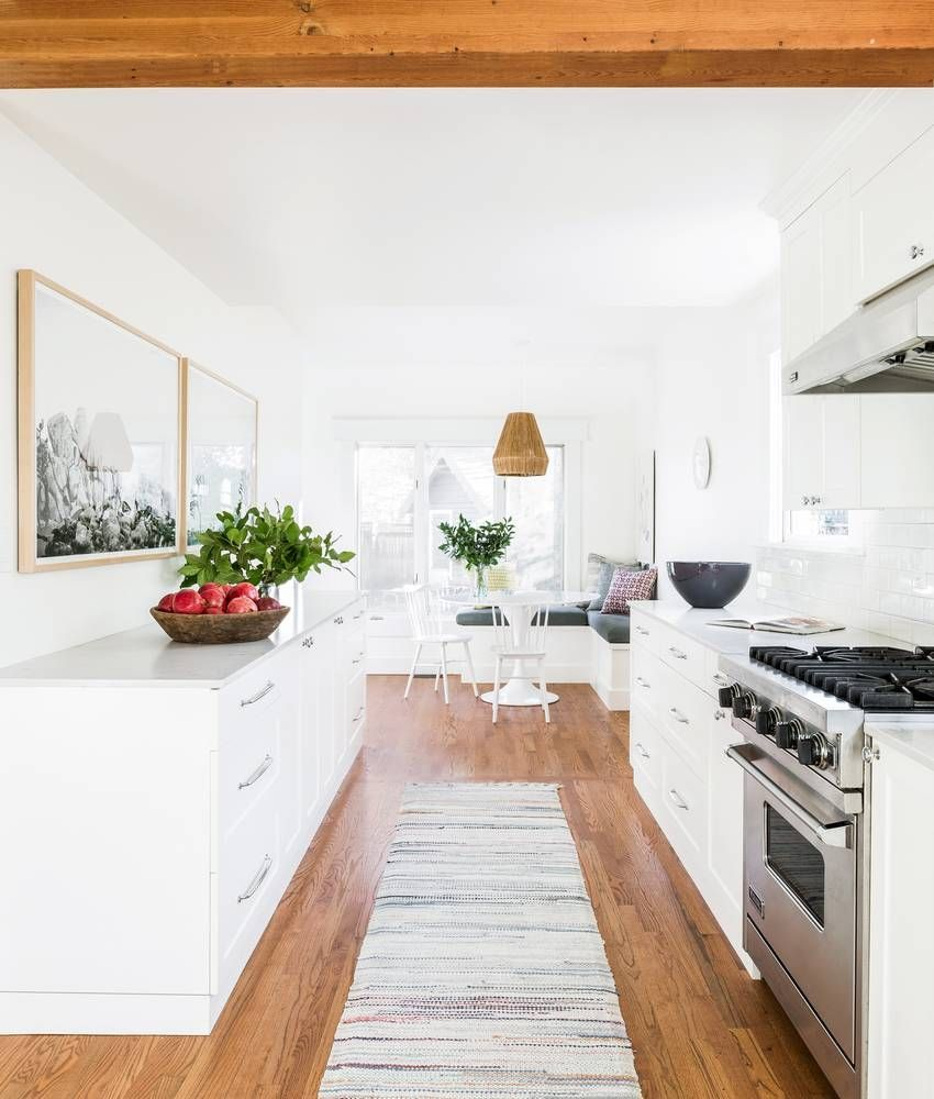 The way this galley kitchen opens up to a small eat in area makes ...