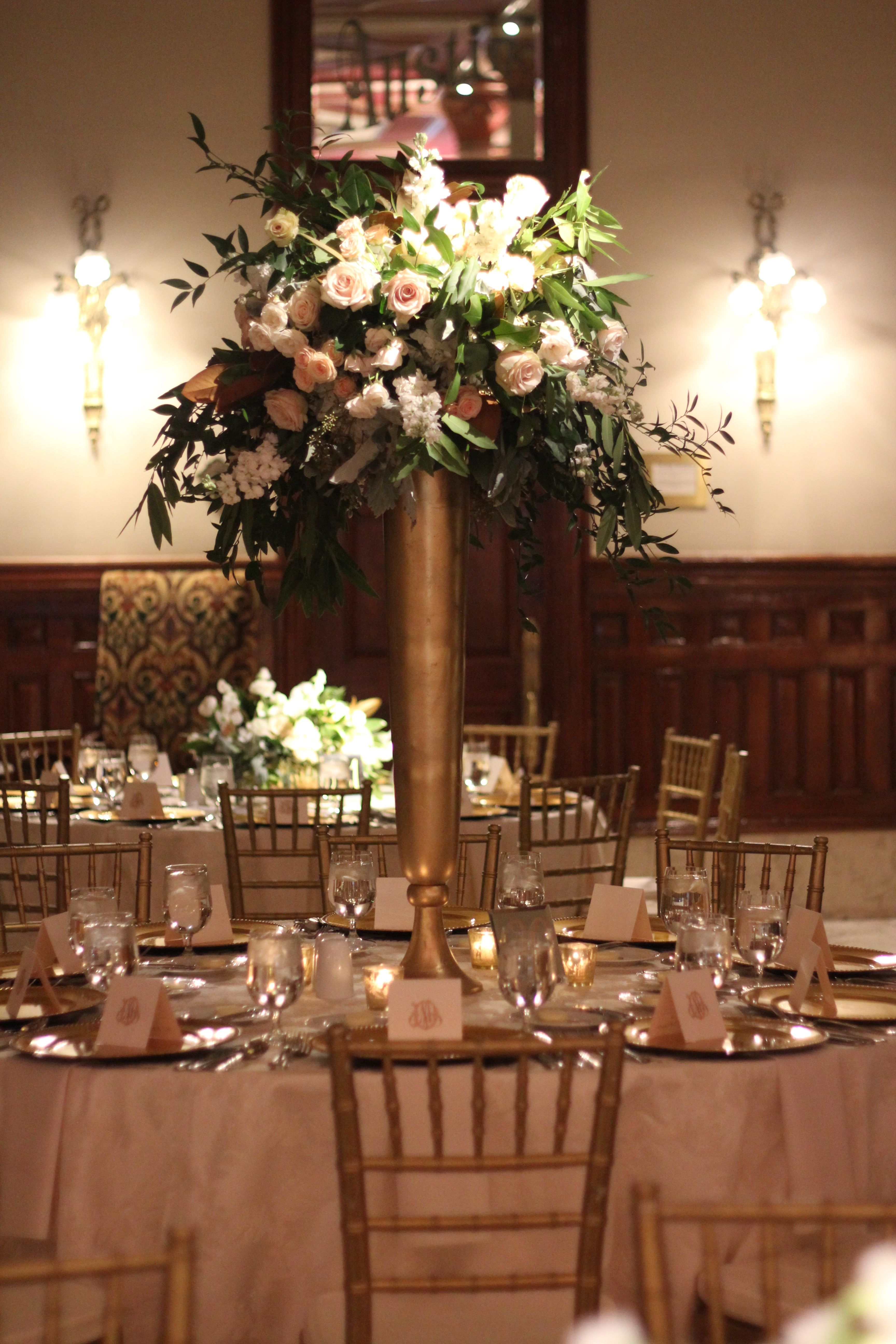 The round tables will have tall gold vases filled with magnolia another option for the tall centerpiece using our tall gold metal vase on the navy blue linens with a beautiful fresh flower design to match reviewsmspy