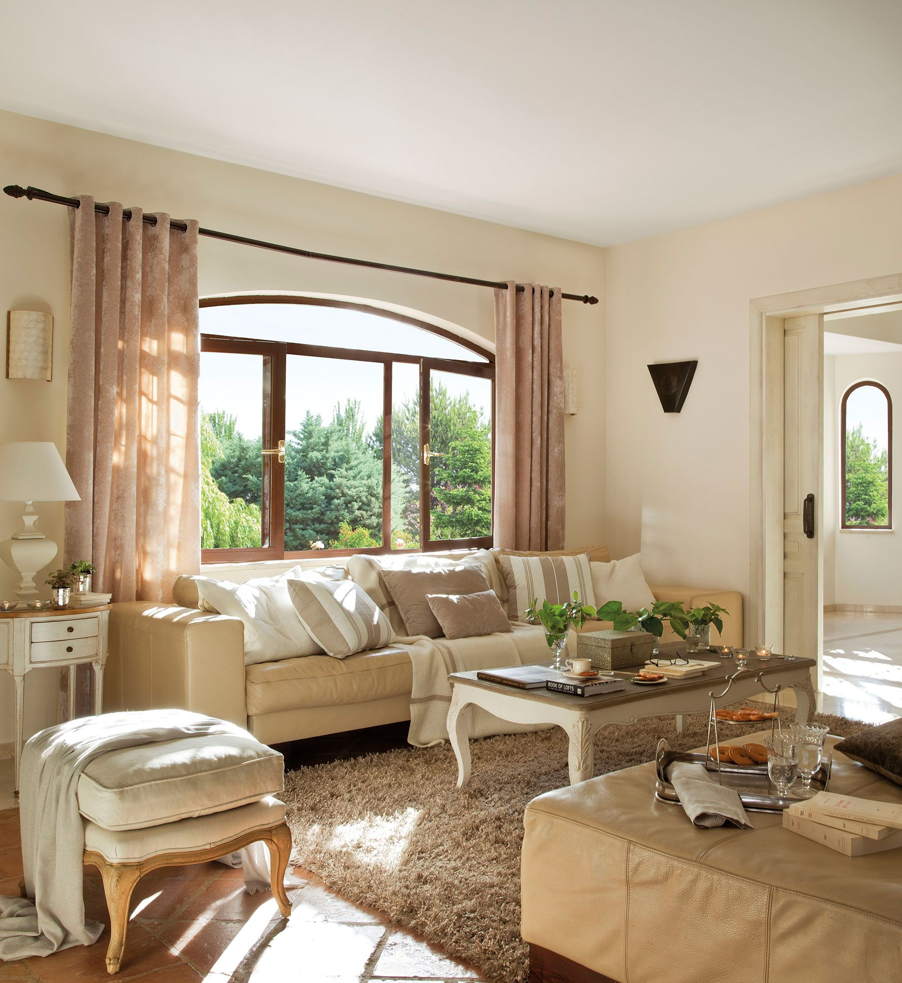 Sal n en tonos beige con ventana en arco decoraci n - Decoracion salones grandes ...