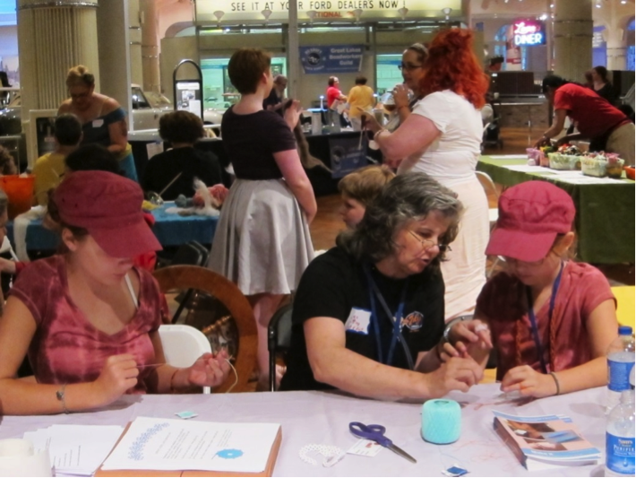 NeedleArts Zone at 2014 Detroit Maker Faire: These two young ladies made the rounds of the entire area, learning everything — including finger-knitting, which wasn't even on the roster!