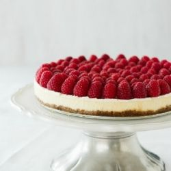 A light and creamy cheesecake with fresh raspberries and raspberry coulis