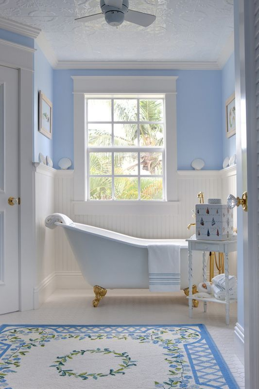 Enchanting robin's egg blue and crisp white bathroom with a dainty slipper tub, bead-board half-wall and a pretty rug.