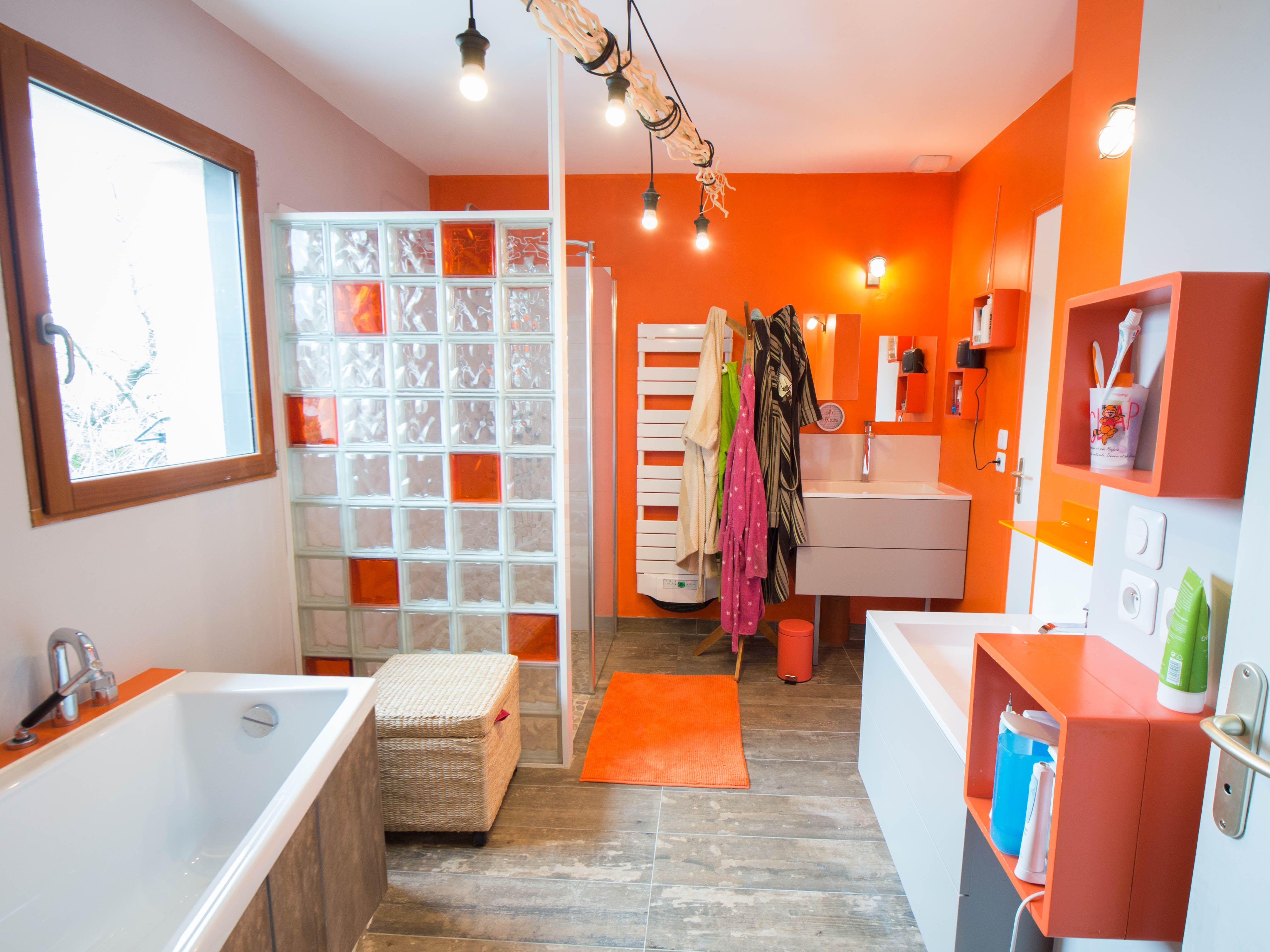 Une salle de bains colorée avec du orange et des briques de couleurs ...