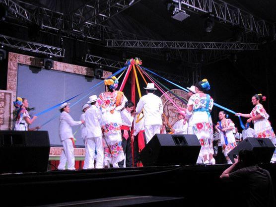 """DANZA DE LOS LISTONES, El dicho baile trata de tejer mientras bailas un tubo en donde los listones se encuentra sujetado en la parte superior del tubo, con pasos y la musica el baile llamado """"cabeza de cochino"""" es realizado."""