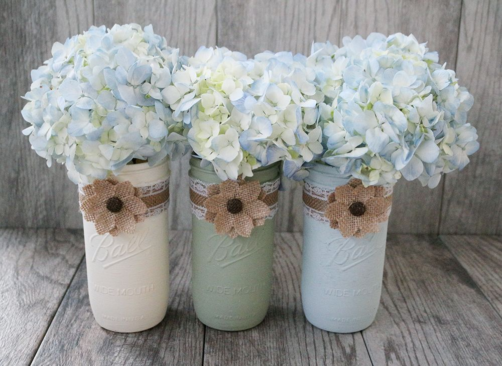 Bring the country warmth and charm to your home or wedding with these Rustic Mason Jars! They are sure to liven up any room or wedding event. Each jar is wrapped with a laced burlap band and embellished with a burlap flower. The flowers come in two colors- brown or white and mason jars are also customizable in twelve stunning colors.