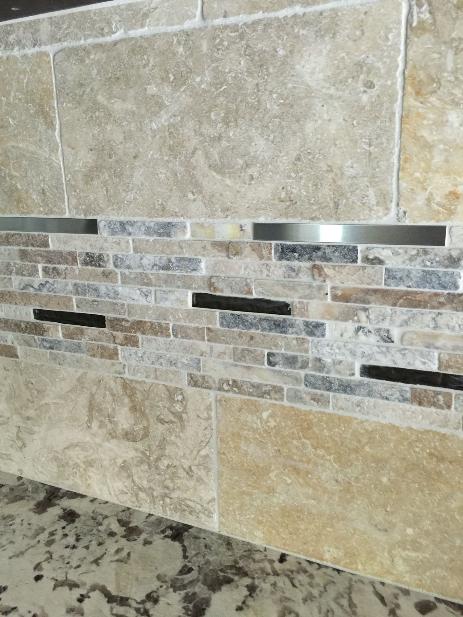 Backsplash. Tumbled limestone with mosaic inset