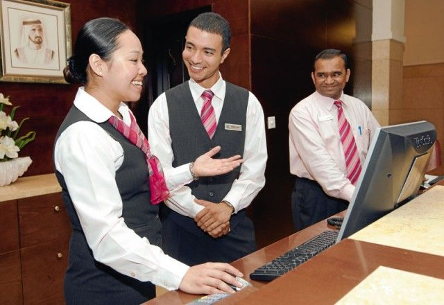 Front Desk Agents With Black Vests And Coordinating Scarf Tie