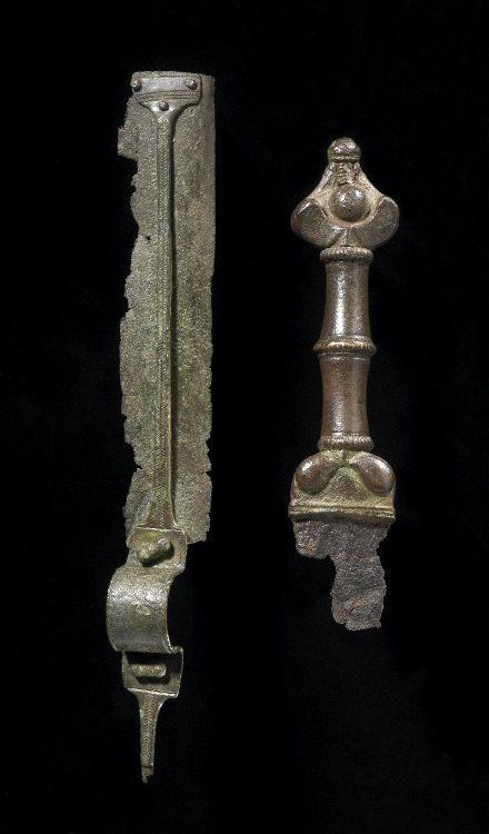 Remains of an iron sword and part of its copper-alloy scabbard. Culture/period:      Iron Age - 200 BC - AD 100 (circa).        Found: England. | © Trustees of the British Museum