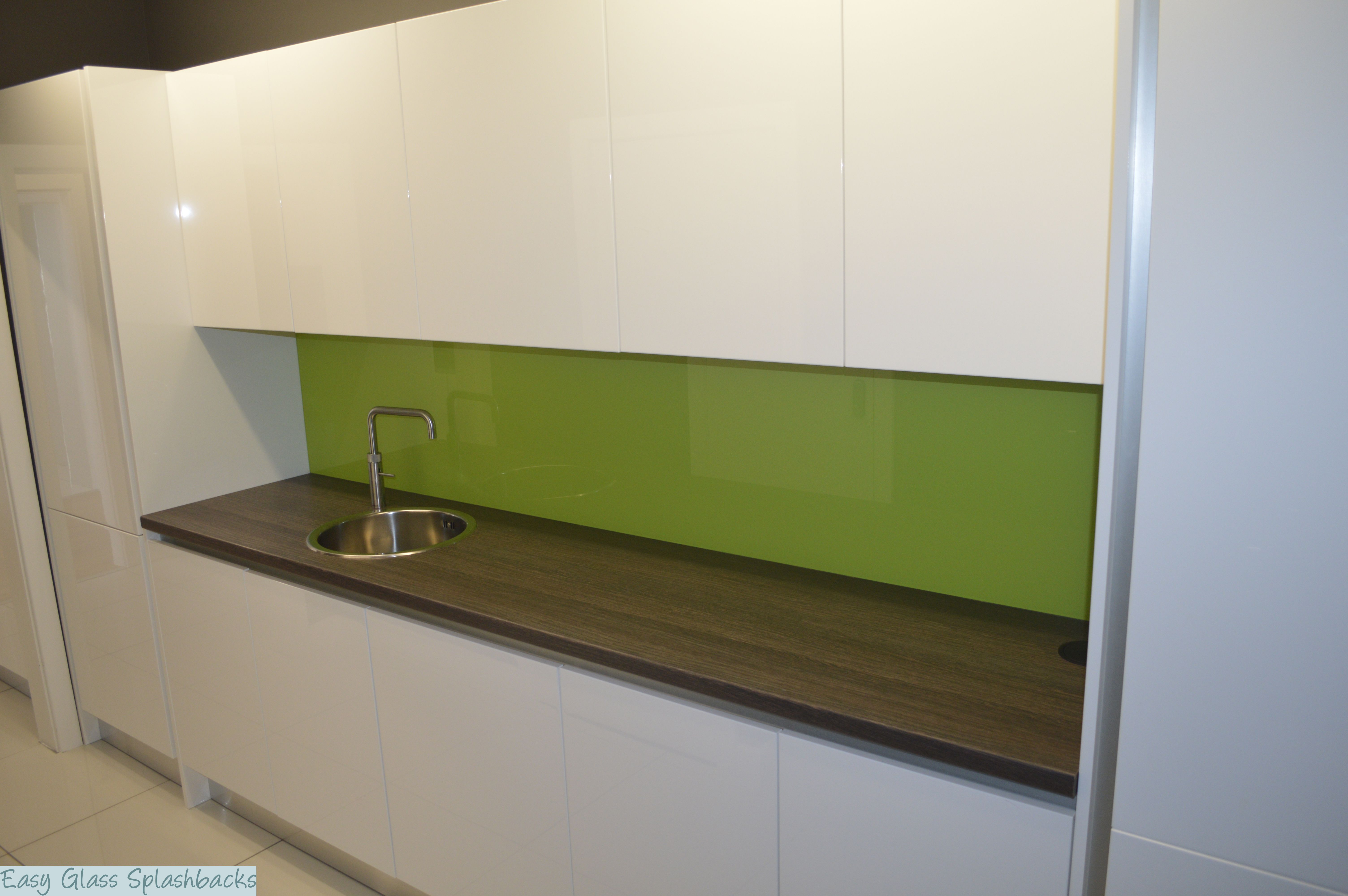 Lime Green Coloured Glass Splashback In A White Kitchen With Wooden