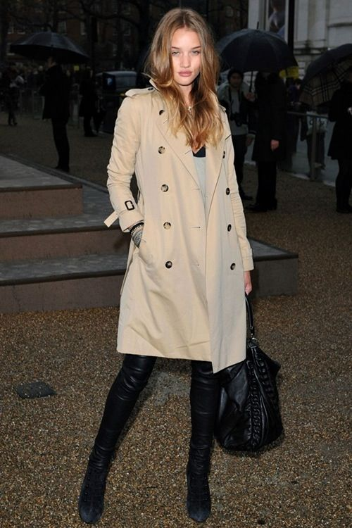 classic  Rosie looking London chic in a trench coat with black leather jeans, boots, & bag.